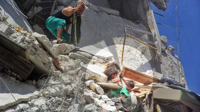 Riham, 5 ans, retient sa petite soeur de 7 mois suspendue dans le vide avant de mourir: cette photo prise en Syrie fait le tour du monde
